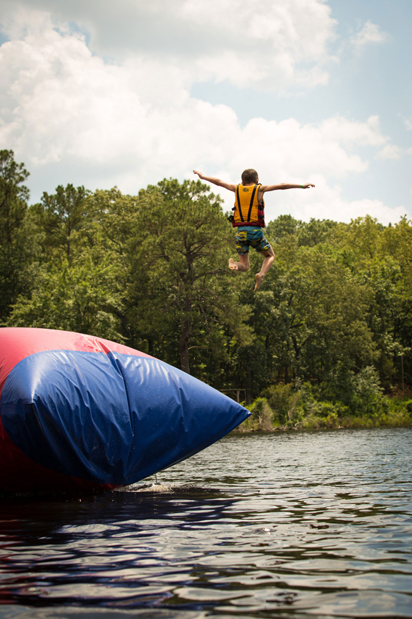 Camper jumping off of the blob into a lake.
